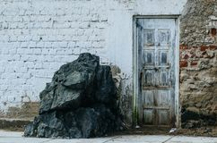 Old door of a house on the edge of the white beach with a large rock next to it. royalty free stock photos