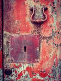 Old door keyhole and handle. Re handle and keyhole on old red wooden door royalty free stock images