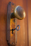 Old Door knob with key. Old brass door knob with key inside the keyhole stock photo