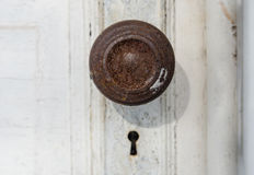 Old door knob and key hole. Rusty door knob and empty key hole on white wood door with peeling paint royalty free stock photo