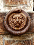 Old door knock. Ancient iron snake and lion sculpture used in order to knock to the palace gates in medieval age stock photos