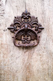 Old door knocker. An old european metallic knocker on a wooden door with nice texture Royalty Free Stock Images