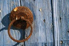 OLd door knocker. Old brass ornamental door knocker on wood door Stock Image