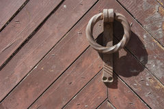 Old door and knocker. An old door with a rusty cast iron knocker stock photography