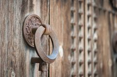 Old door knocker. Ancient iron door knocker on medieval house Royalty Free Stock Image