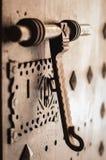 Old door knocker. Ancient iron door knocker on medieval house Stock Photography