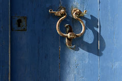 The old door knocker on the blue. Royalty Free Stock Photography