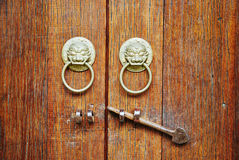 Old door and knocker. Closeup of red old wooden door and yellow copper lion knocker Royalty Free Stock Images