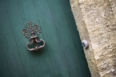 Old door knocker. Knocker on the green door of a French mansion Stock Photos