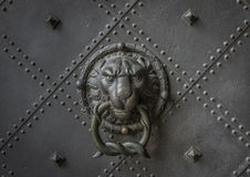 The old door knocker on a iron door Stock Images