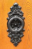 Old door knocker. On wooden background royalty free stock images