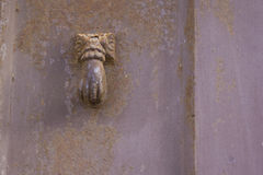 Old door knocker shaped by hand. Old and corroded metal door knocker shaped by hand Stock Photos