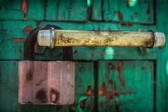 Old door lock handle. Wood cracked paint green door lock Stock Image