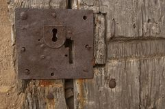 Old door with lock and nails stock photography