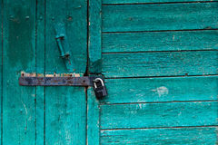 Old door locked up.Bright turquoise peeling paint. Old wooden building. Stock Photography