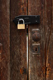 Old door with new padlock. Old wooden door with shiny new padlock Stock Photography