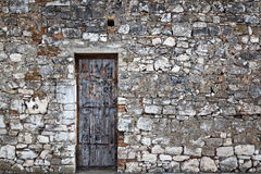 Old door in an old stone wall Stock Images