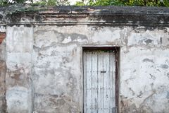Old door on the old wall. Old wooden door is locked on old plaster walls Stock Photos