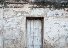 Old door on the old walls. Old wooden door is locked on old plaster walls Royalty Free Stock Photos