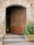 Old door with rampant wooden arch ajar. Old door of rampant wooden arch ajar with iron nails in Ainsa, Huesca, Aragon Stock Photo