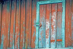 The old door on the red wooden wall. Part of an old building of boards and a closed door Royalty Free Stock Photos
