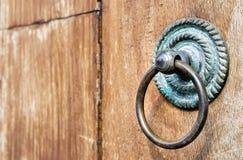 Old door ring handle on brown wooden door Stock Images