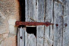 Old door with rusty bolt, lock. Rusted, oxidized. Hinge. Old wood. royalty free stock photography