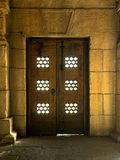 Old door in stone building and sunlight penetrates Royalty Free Stock Images