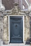 Old door with a stone ornament on top Stock Photography