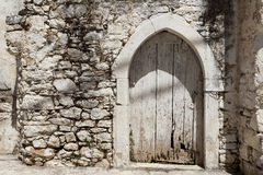 Old door in the stone walls of the village houses. Excellent background. Stock Images