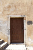 Old door in the stone walls of the village houses. Excellent background. Royalty Free Stock Photos