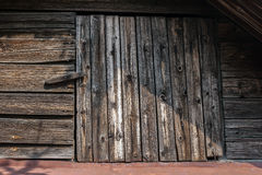 Old door to the attic of pine boards with a latch. Converted grown old under the influence of weather Stock Photos