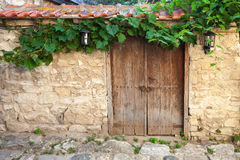 Old door and vine on stone wall, Nessebar Royalty Free Stock Photo
