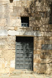 Old door and window in ancient stone wall in Greece. Old stone wall with solid wooden door and window above on Greek Island of Kos royalty free stock photos