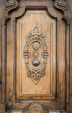 Old door of wood with patterns carved on it. Royalty Free Stock Images