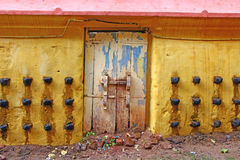Old door and yellow wall of an ancient Hindu temple with oil lamps Stock Photography