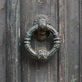 Old doorhandle on green wooden door Stock Photos