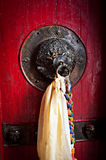 Old doorknob decorated with tassel Stock Photo