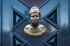 Old doorknob in the form of man head on a blue door Stock Photos
