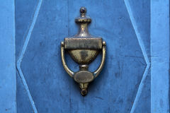Old doorknocker from brass on a blue  door Royalty Free Stock Image