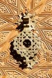 Old doorknocker from Morocco. Brass doorknocker at a decorative carved door in Marrakesh, Morocco Stock Photo