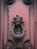 Old doorknocker on pink door. Old doorknocker with the garlanded head of a man or demon mounted on an old wooden door with a light coating of pink paint Stock Image