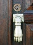Old doorknocker in the shape of a hand and brass keyhole. In an old brown wooden door in spain Stock Photos