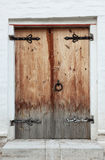 Old doors. Old wooden door with shod door hingeds against a white brick wall Stock Image