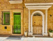 The old doors of Birgu, Malta. The old mansions of Birgu boast traditional colored wooden doors, decorated with gilt fish-shaped handles, Malta stock images