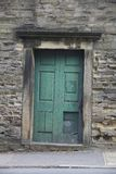 Old doorway at abandoned building. Old green doorway at abandoned building with stone wall royalty free stock image