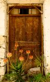 Old doorway with flowers in Mediterranean village Royalty Free Stock Photography