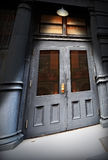 Old doorway under light. Dark, old creepy doorway or entrance to a building under a single bright light Royalty Free Stock Images