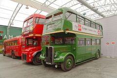 Old double decker buses at brooklands museum, england. Old double decker red and green buses parked under a covered roof at the london bus museum, brooklands, uk Royalty Free Stock Photography