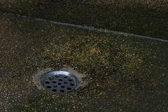 Old drain hole with black stone background.  Stock Photos